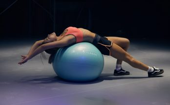 young woman balancing on a yoga ball
