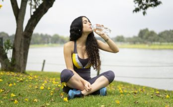 woman drinking water after working out in the park