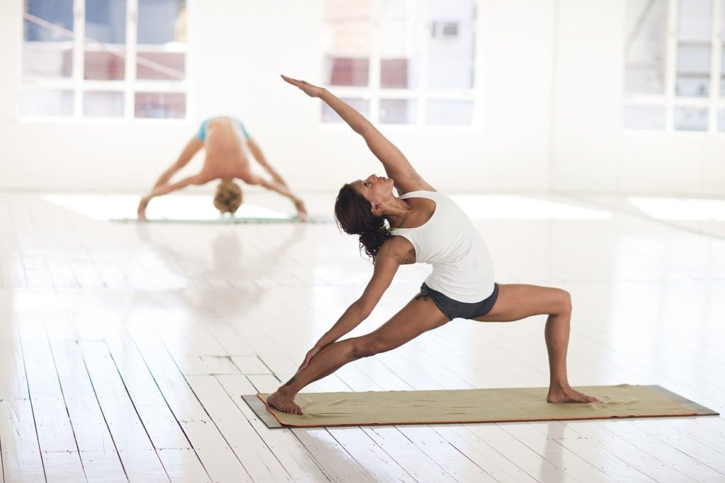 women performing yoga stretches