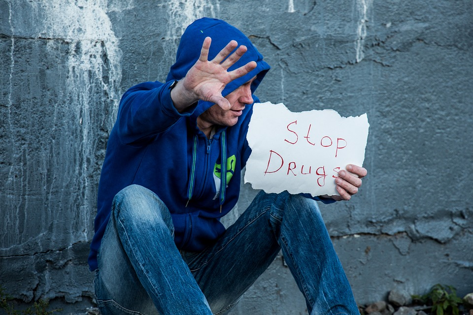 man holding stop drugs poster