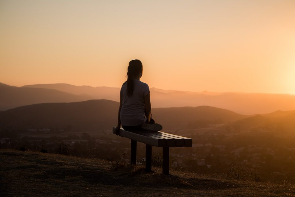woman sitting alone looking at the horizon