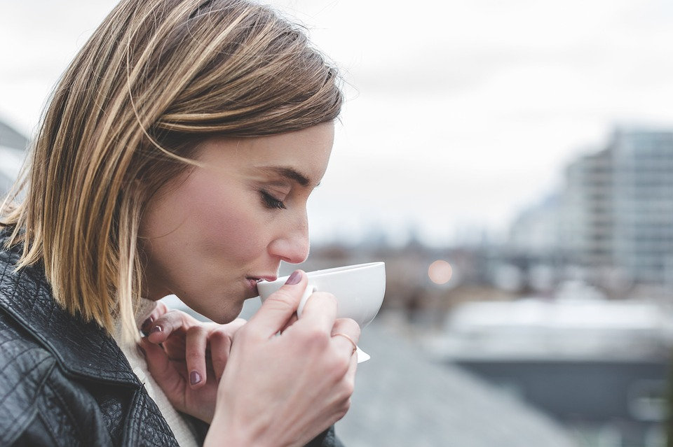 woman drinking from a white cup outside and smelling the coffee