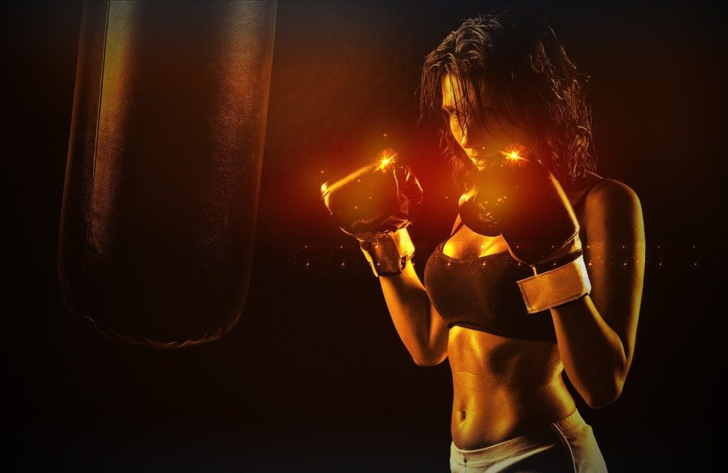 woman doing boxing workout with red gloves and punch bag