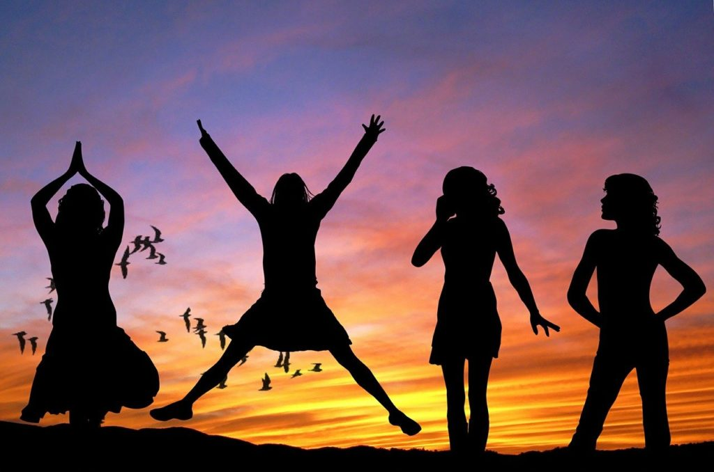 4 women silhouetted against a sunset doing exercise and yoga