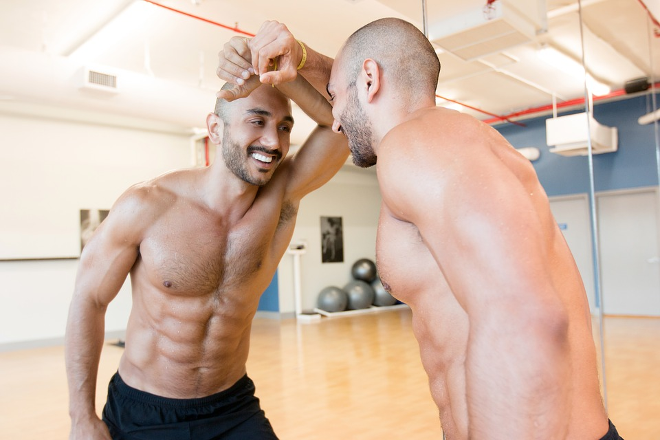 man leaning on mirror in a gym with fit body, abs and smiling