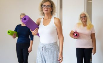 3 women about to exercise with yoga mats