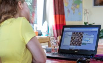woman playing chess online on a laptop at home