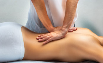 Close up of physiotherapist applying pressure with hands on female back. Young woman lying on spa bed facing down.