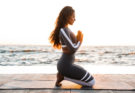 Photo of strong young fitness woman outdoors in the beach make yoga meditate exercises.