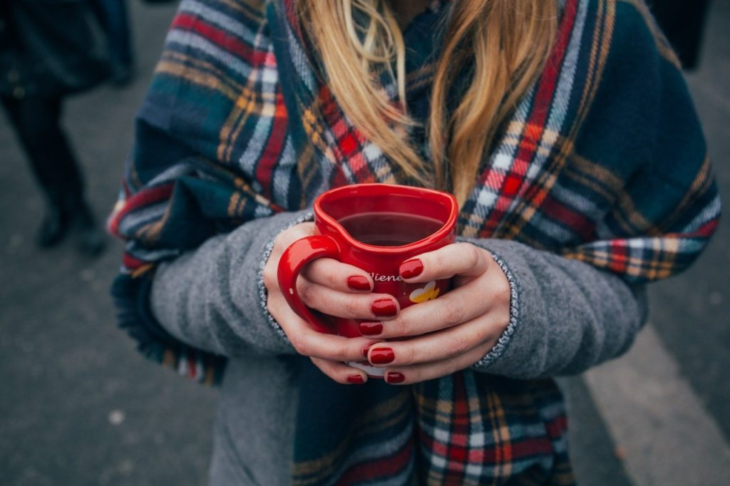 woman with good nails holding a heart shaped mug
