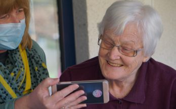 elderly person in care home looking at phone