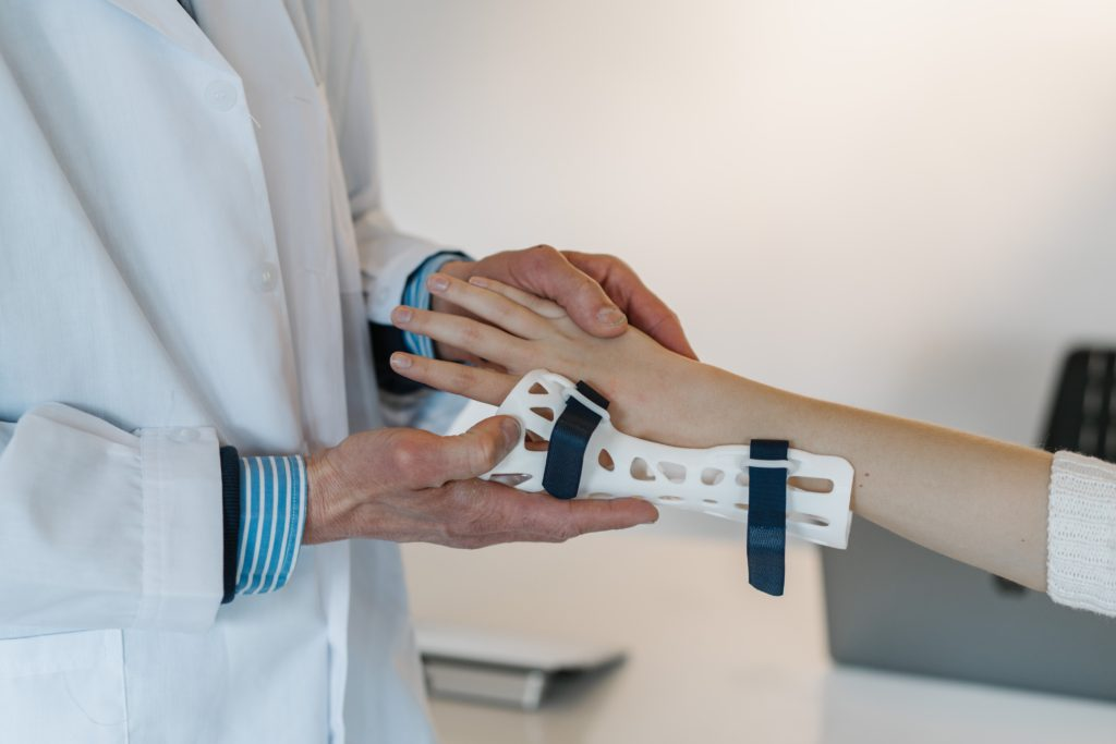 person with wrist pain having a support fitted