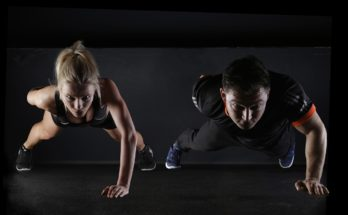 Fitness couple doing one hand push ups together