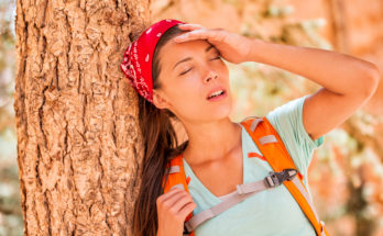 Dehydrated woman outside leaning against a tree
