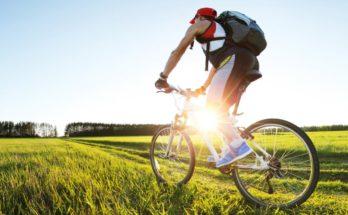 man riding hybrid bike over grass with sun shining through the frame