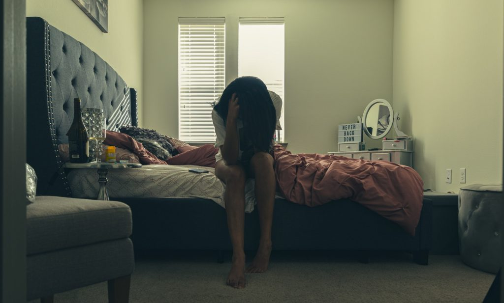 woman suffering from depression sitting on bed with head in hands