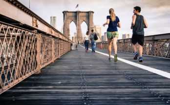 people running in the city over a bridge