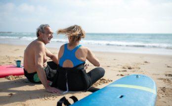 senior couple on the beach with surfboards