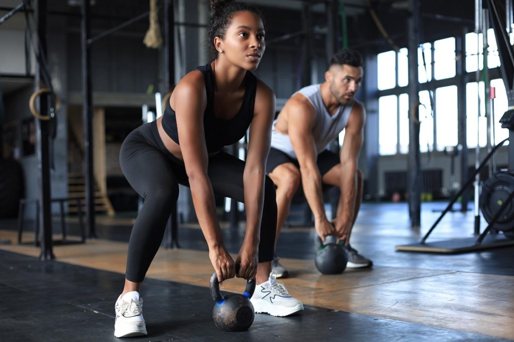 woman and man working out with kettlebells