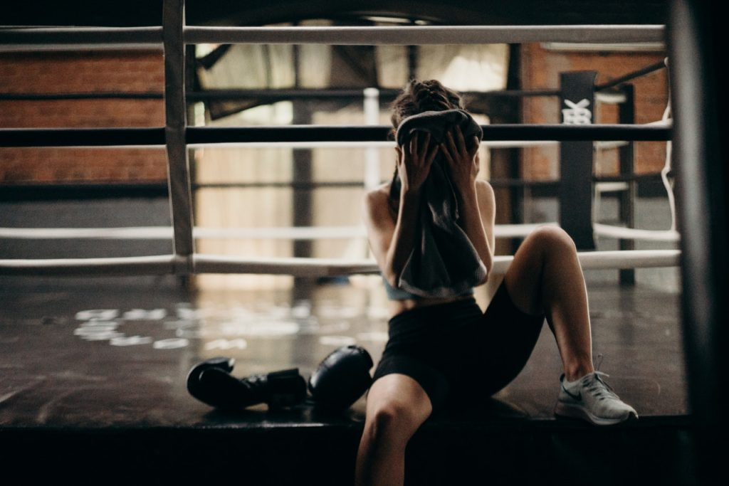 woman exhausted on edge of boxing ring