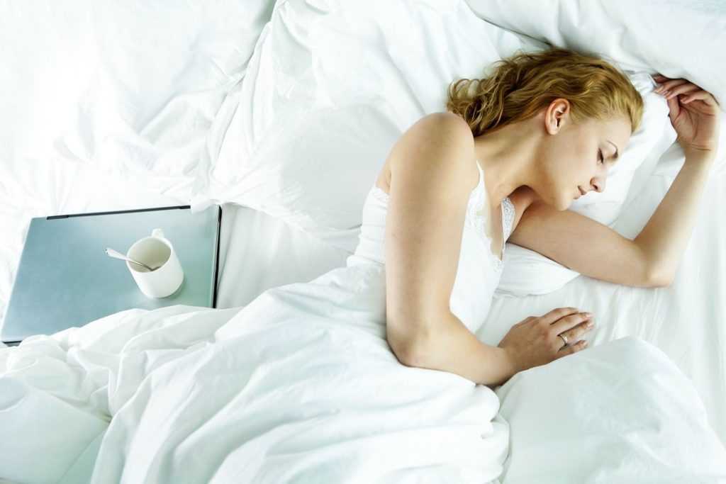 woman sleeping in bed with laptop
