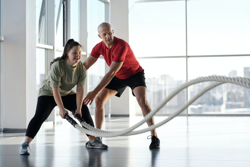 fitness trainer teaching woman to use workout ropes