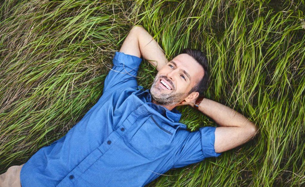 man laying in grass smiling