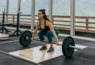 woman weight lifting with mountains behind