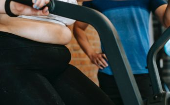 woman with belly fat on an exercise bike