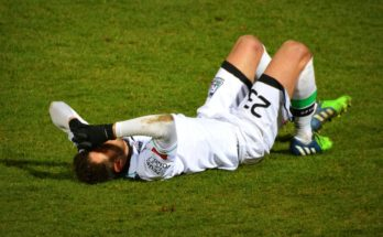 injured footballer laying on the grass with hands on face in pain