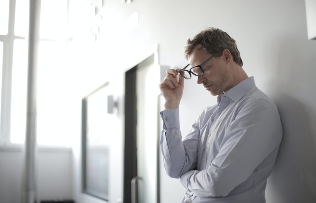 man standing in corridor holding glasses looking stressed